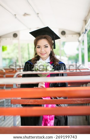 Beautiful asian woman graduating holding flower and smiling on bus - stock photo