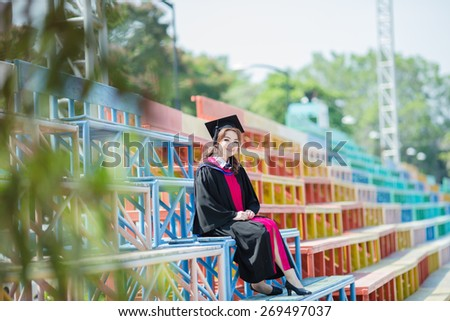 Beautiful asian woman graduating sit down on grandstand and smiling - stock photo