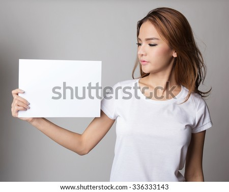 Beautiful asian woman holding blank card or paper, presenting and showing. - stock photo