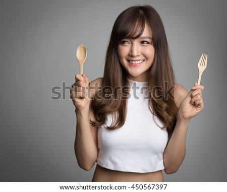 Beautiful asian woman holding spoon and fork, looking to side to copy space. - stock photo
