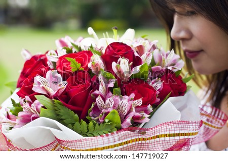 Beautiful Asian woman in love holding flower bouquet. - stock photo