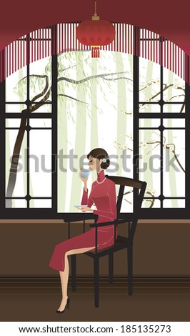 Beautiful Asian woman in traditional Chinese dress sitting and drinking tea - stock photo