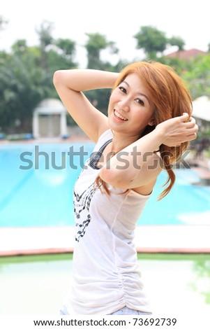 beautiful asian woman is posing on the pool - stock photo