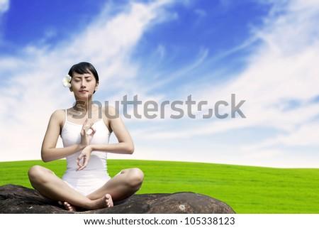 Beautiful Asian woman meditating in meadow - stock photo