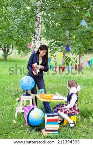 Beautiful asian woman mother teacher talking reading book to schoolgirl outdoors, back to school - stock photo