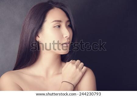 Beautiful asian woman on black background - stock photo