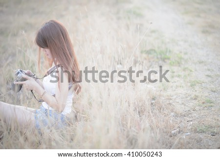 beautiful asian woman photographer holding camera seat in clump of grass with sunset time - stock photo