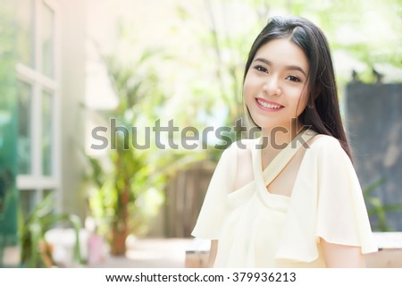 Beautiful Asian woman smiling in the green park - stock photo