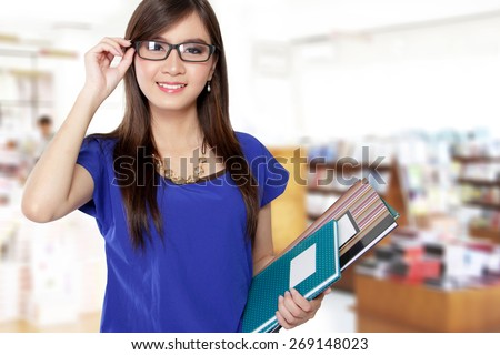 Beautiful Asian woman smiling while holding her glasses and some books in a library - stock photo