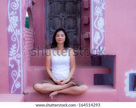 Beautiful asian woman training yoga and meditating, sitting on a pink stairs with  arabian architecture background - stock photo