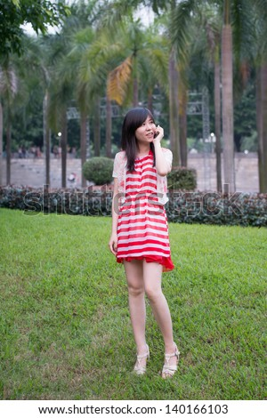 Beautiful Asian woman using cell phone outdoor - stock photo