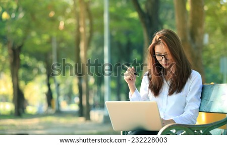 beautiful asian woman using laptop computer in the park - stock photo