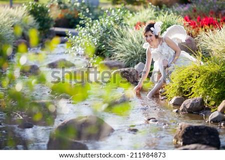 beautiful asian woman wear white dress,angel wing,bride in the forest,sunshine daylight - stock photo