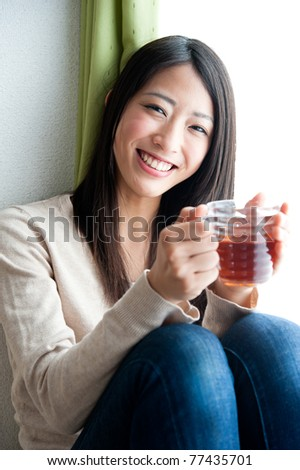 beautiful asian woman with a glass of tea - stock photo