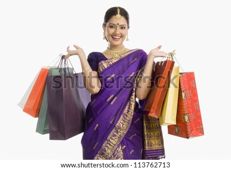 Beautiful Assamese woman holding shopping bags and smiling - stock photo