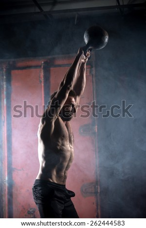 Beautiful athlete doing kettlebell swings. Profile picture. Athlete bare-chested. Studio shot in a dark tone. - stock photo