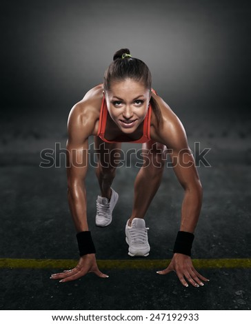 beautiful athlete on low start on a dark background isolated with clipping path - stock photo