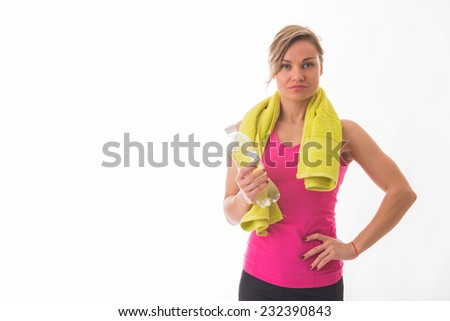 Beautiful, athletic blonde posing on a white background with a towel around his neck and a bottle of water in hand. Sports, fitness, exercise, beautiful figure - the concept of a healthy lifestyle. - stock photo