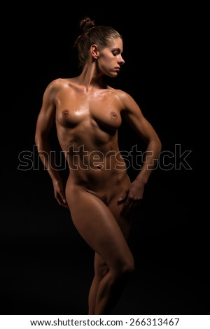Beautiful athletic brunette standing nude in deep shadow - stock photo