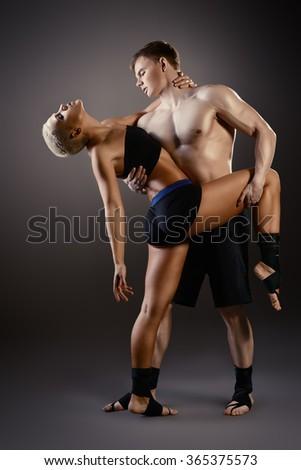 Beautiful athletic couple posing together over black background. Gymnastics, fitness, bodybuilding.  - stock photo