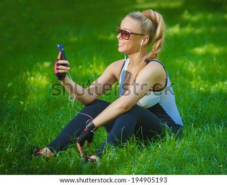 beautiful athletic girl listening to music while sitting on the grass in the park - stock photo
