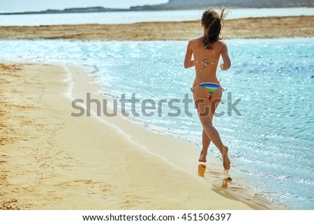 beautiful athletic woman dressed in bikini running on the beach along the sea front - stock photo