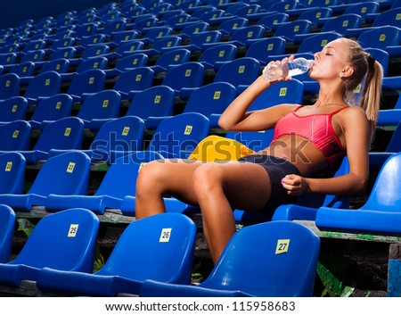 Beautiful athletic woman in a sports suit sitting on a seat and drink water from a bottle - stock photo
