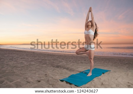 Beautiful athletic woman practicing energizing and relaxing yoga exercises on a colorful sunrise on the beach - stock photo