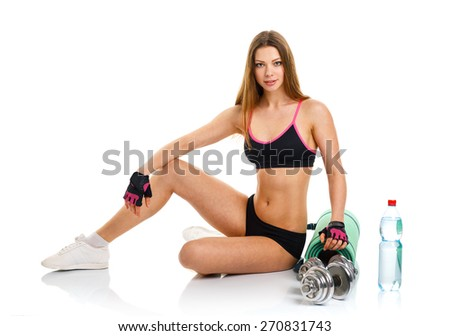 Beautiful athletic woman with dumbbells, mat for fitness, a bottle of water sitting on white background - stock photo