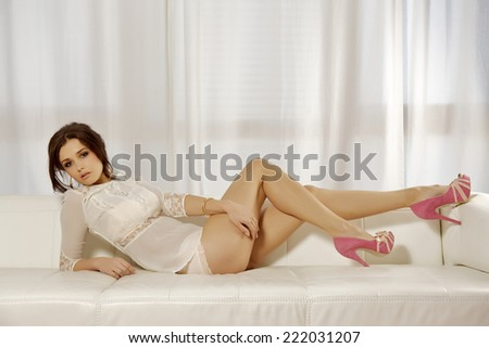 Beautiful attractive and sexy young adult sensuality brunette pretty woman on the white sofa in luxury style apartment - stock photo