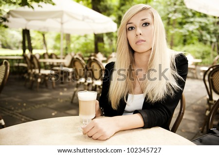Beautiful attractive blonde drinking coffee - stock photo