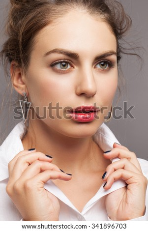 Beautiful attractive charming model with dark hair, perfect clean skin and nude makeup posing in studio on grey background, wearing white shirt. - stock photo