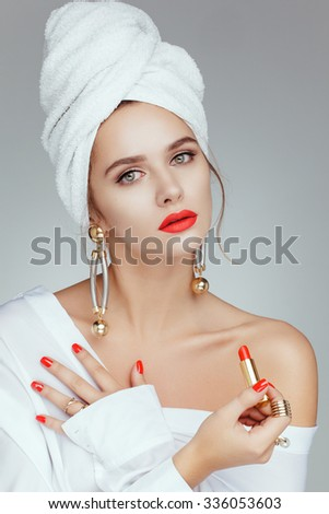 Beautiful attractive charming white caucasian model girl posing in white towel on her head, taking red lipstick. Red lips and red nails. - stock photo