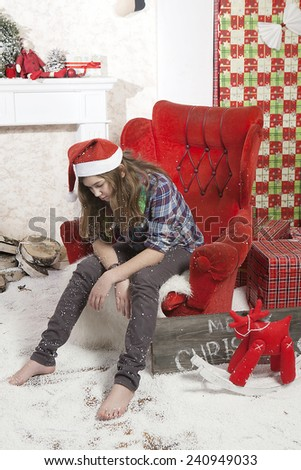 Beautiful attractive sad disappointed brown haired girl in Santa hat sitting in the chair near fir tree and heap of presents in different gift wrapping on white pile carpet - stock photo