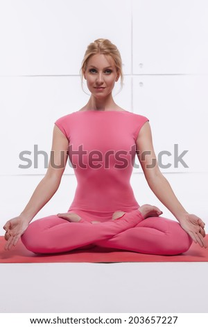 Beautiful attractive sexy blond woman doing yoga sitting in the lotus position relaxes and opens the chakras dressed in comfortable fitting suit pink - stock photo