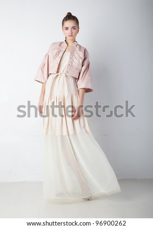 Beautiful attractive supermodel - young woman in elegant fashion dress posing over white wall - stock photo