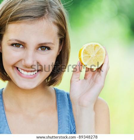 beautiful attractive woman short hair holding park half lemon smiles - stock photo