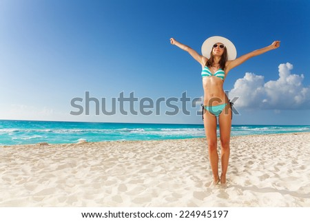 Beautiful attractive woman standing on the beach with lifted hands - stock photo