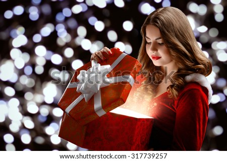 beautiful, attractive, young girl in a red suit Snow Maiden, smiles holding a gift, opens a gift; on a black background, portrait. - stock photo