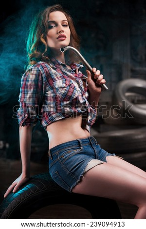 Beautiful auto mechanic. Beautiful young woman holding work tool and looking at camera while sitting at the car tire in auto repair shop - stock photo