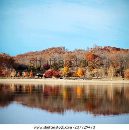 Beautiful autumn landscape with colorful trees, beach, and reflection in lake. - stock photo