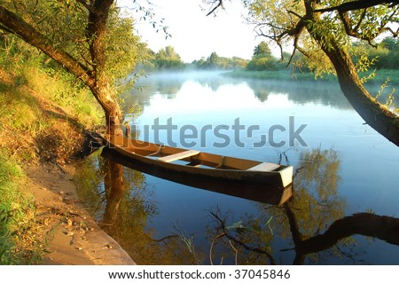 Beautiful autumn river and yellow rowing boat on a tranquil early morning - stock photo
