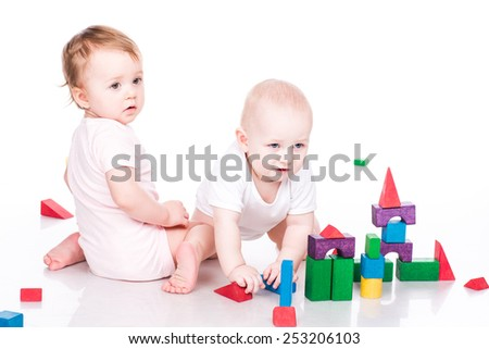 Beautiful babies building a castle with cubes isolated on white - stock photo