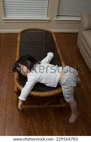Beautiful baby asian toddler girl falls asleep on bamboo table - stock photo