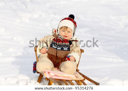 Beautiful baby boy on sledge in winter - stock photo