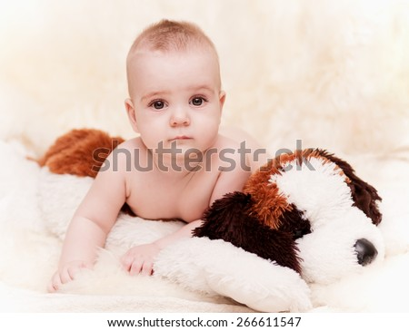 beautiful baby boy with brown eyes lying and soft toy dog kids background, shallow depth of field - stock photo