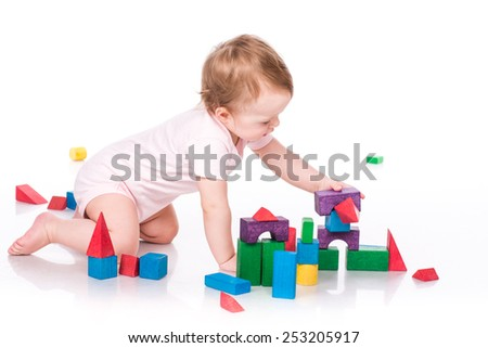 Beautiful baby building a castle with cubes isolated on white - stock photo
