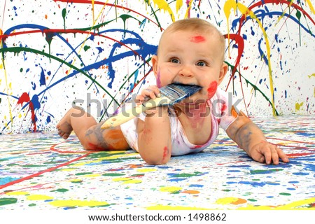 Beautiful baby covered in bright paint with paint brush in mouth. - stock photo