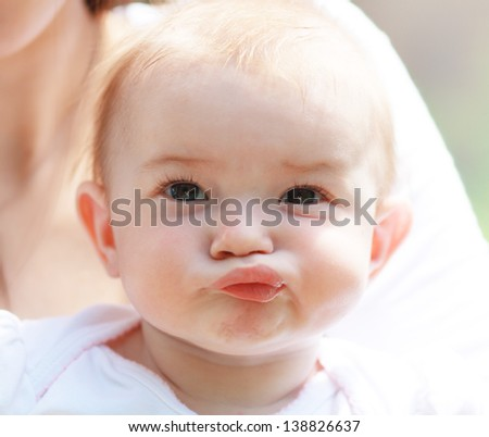 Beautiful baby few months old making face outdoors - stock photo