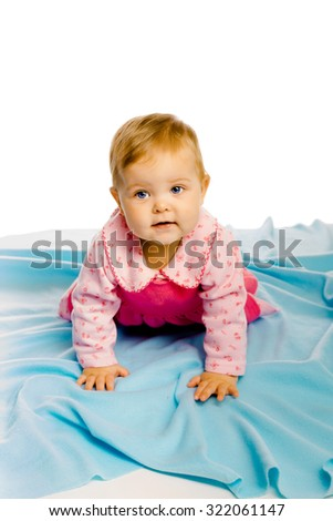 Beautiful baby girl crawling on the blue coverlet. Studio - stock photo